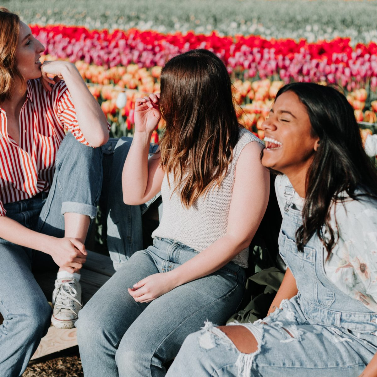 Group of girls laughing in a tulip field.