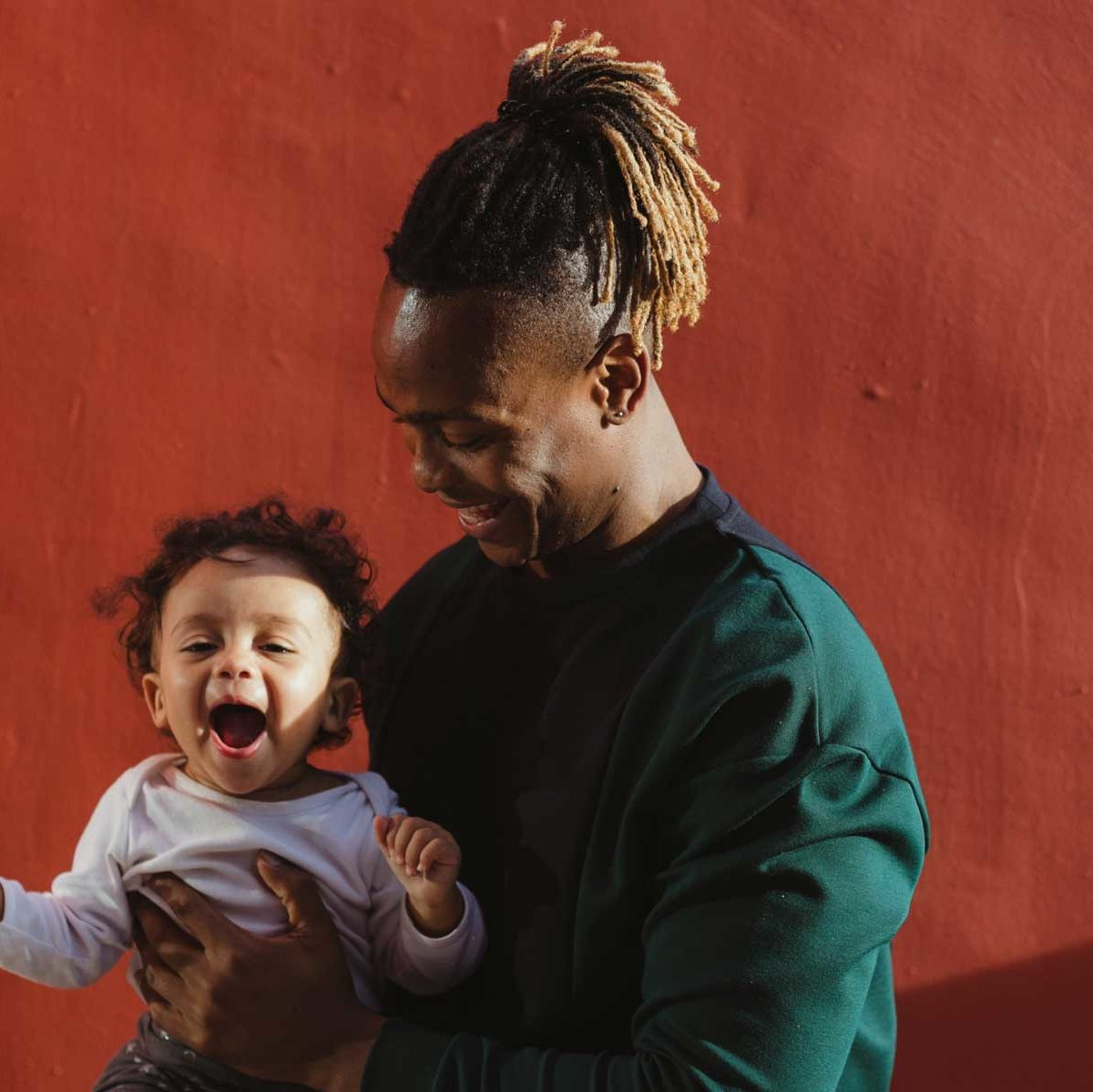 Happy father holds energetic child.