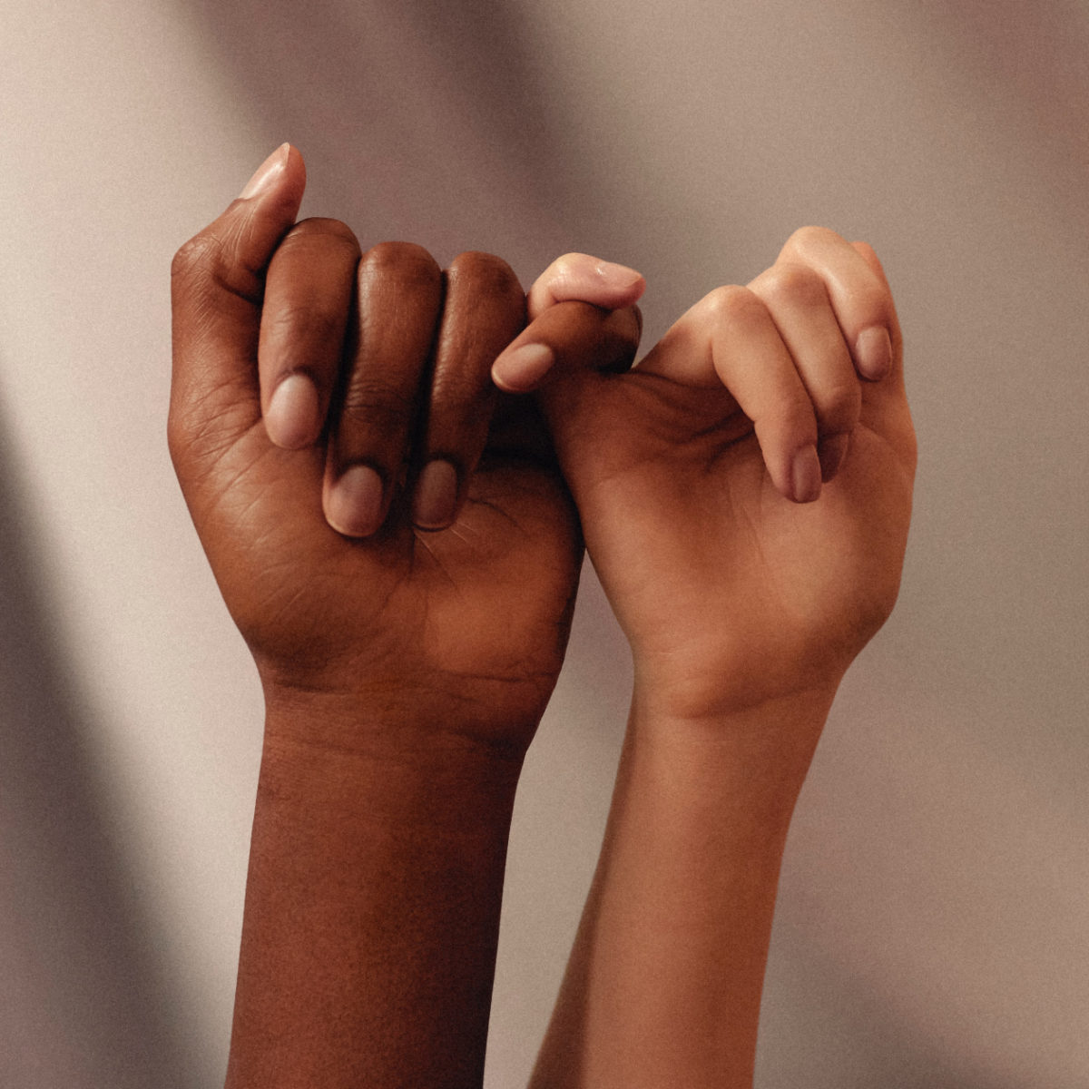 Two women of color with interlocking pinky fingers.